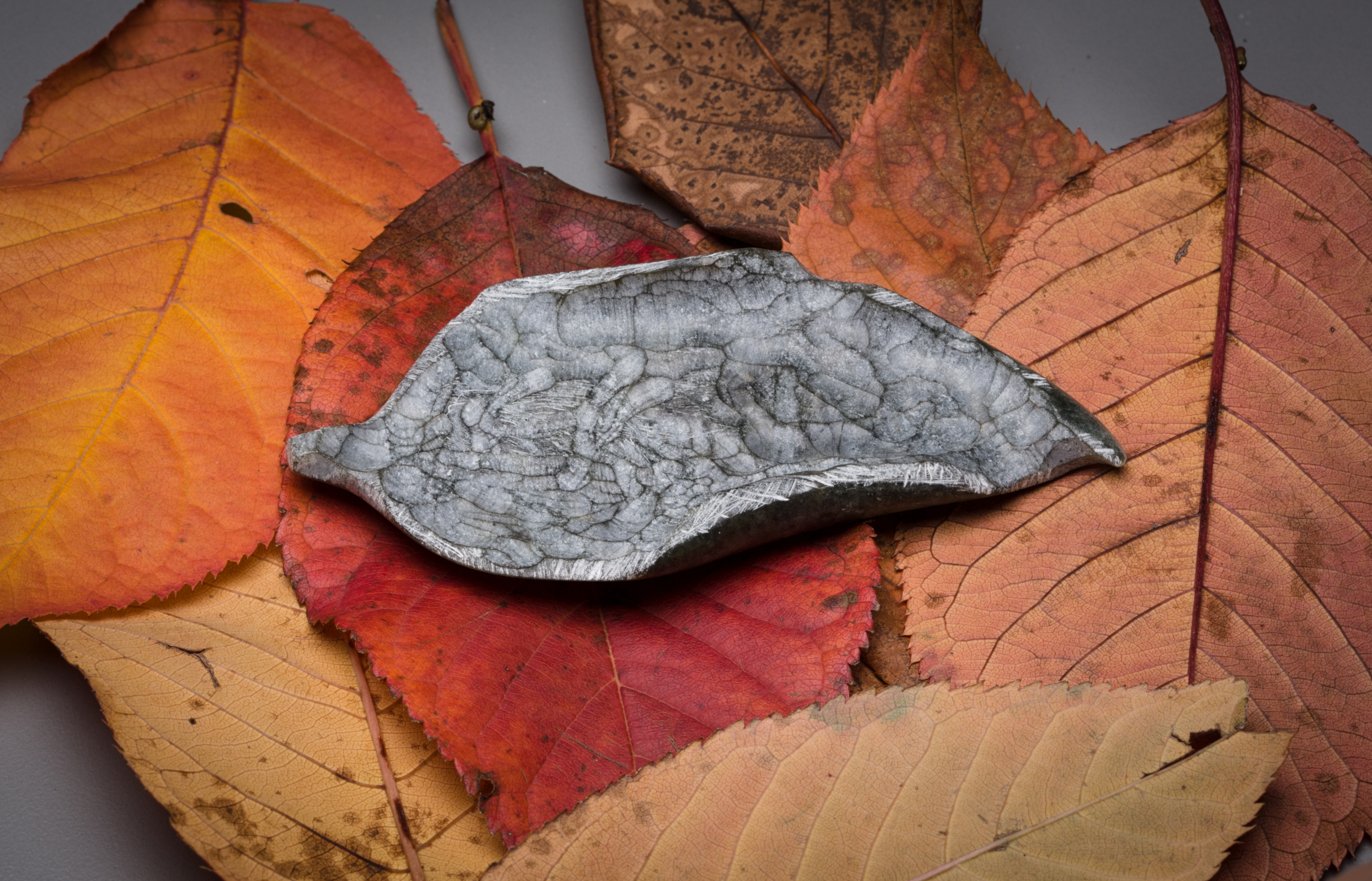 The top is textured and rubbed to mimic the veining of leaves, while the underside is polished to reveal rich greens and greys. Picking up and holding the sculpture is encouraged