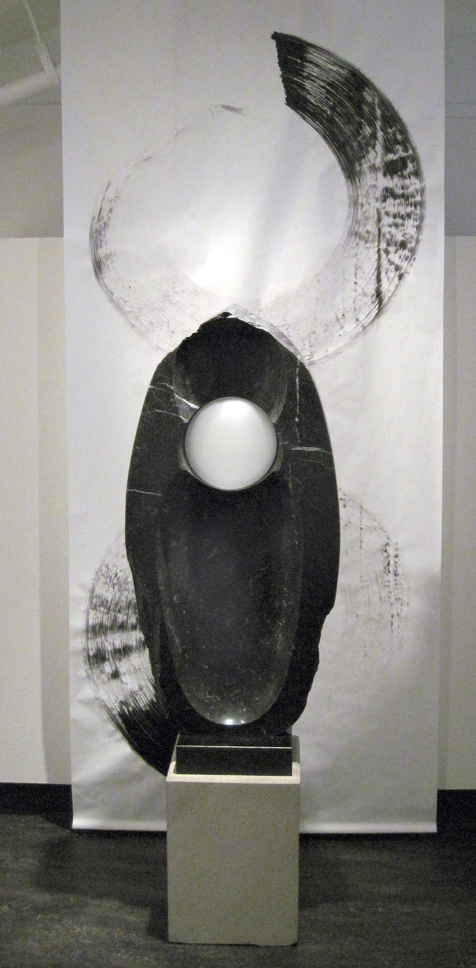 """Black Water Lens"" – Chrysalis, Alaska black fossiliferous limestone, 48"" X 22"" X 7."" Displayed in front of a sumi-e ink painting by Jim Ballard."