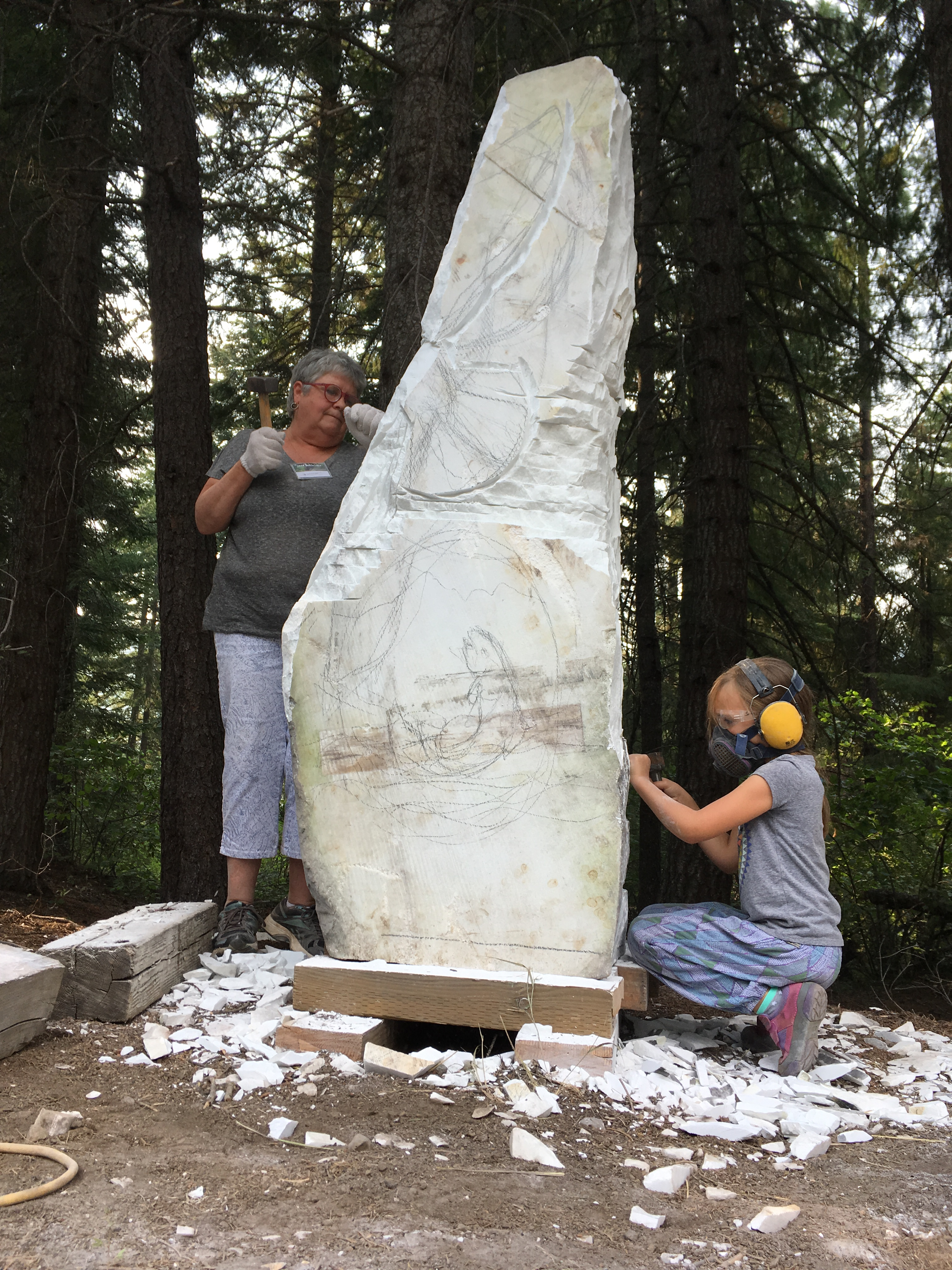Community Stone: Samia Imonen and MJ Anderson carving on the community stone