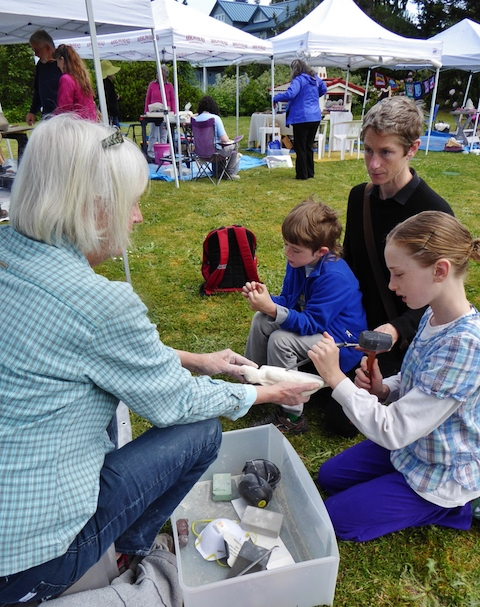 Sculptor Gudrun Ongman shows a young visitor how to carve stone. Photo by Eva Kozun.